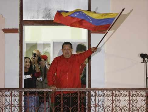 Chavez waves flag to supporters. Photo Courtesy Fernando Llano, AP