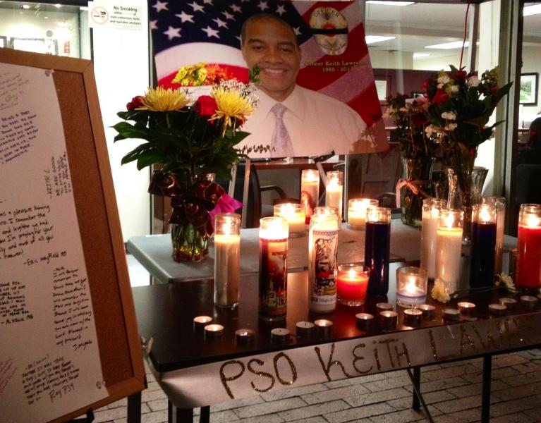 A candlelight vigil honoring Officer Keith Lawrence sits outside the DPS campus headquarters. (Photo by ATVN.)