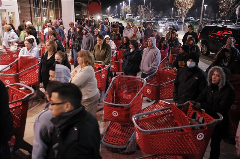 Black Friday shoppers await Target's opening to steal the best deals. (Photo by AP)