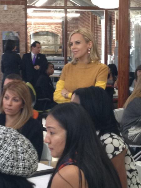 Tory Burch smiles as she listens to other business mentors at Monday's conference.