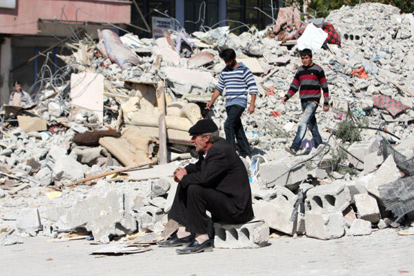 People survey the damage after an earthquake in Turkey left at least 432 people dead.  (AP)