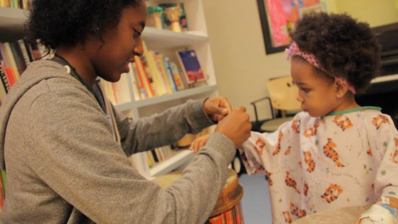 A dancer wraps around the arm of a patient a bracelet they made together (Cameron Qun/ATVN).