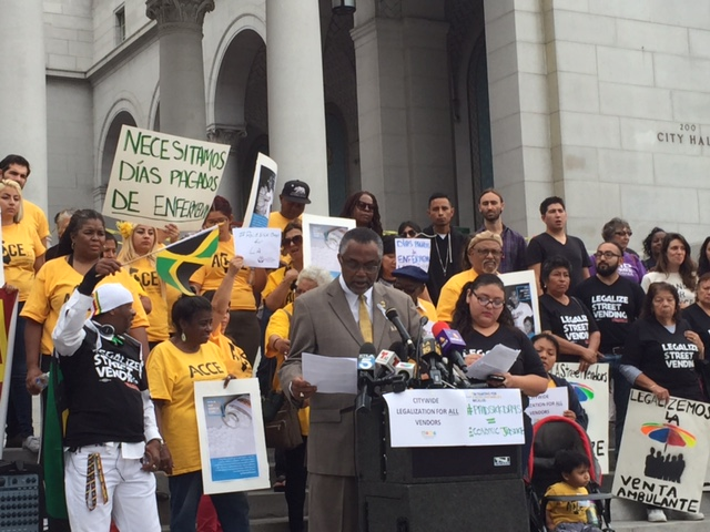 Council Member Curren Price stands with supporters on the steps of City Hall.